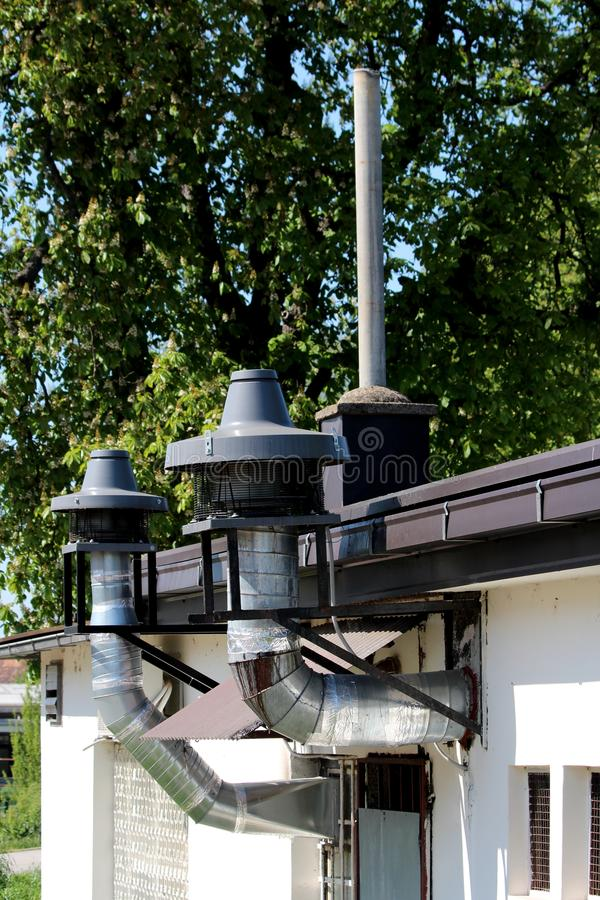 I camini industriali della cucina del ristorante con i grandi filtri e la protezione del metallo in cima hanno montato sul bordo  fotografie stock