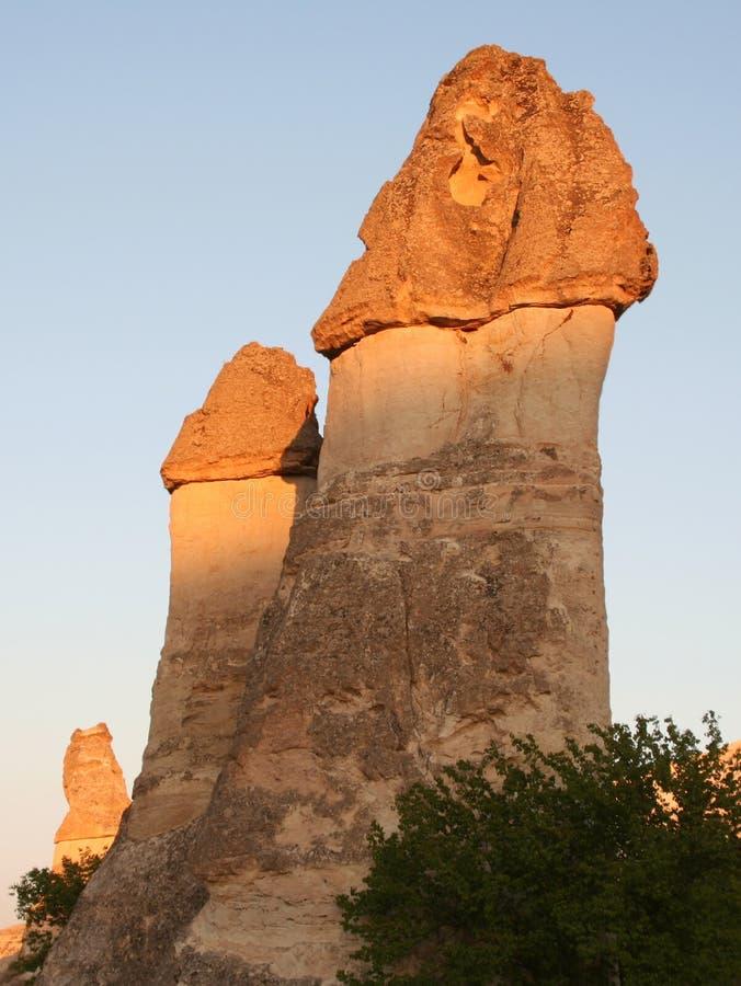 I camini leggiadramente con la sera si accendono in Cappadocia immagine stock libera da diritti