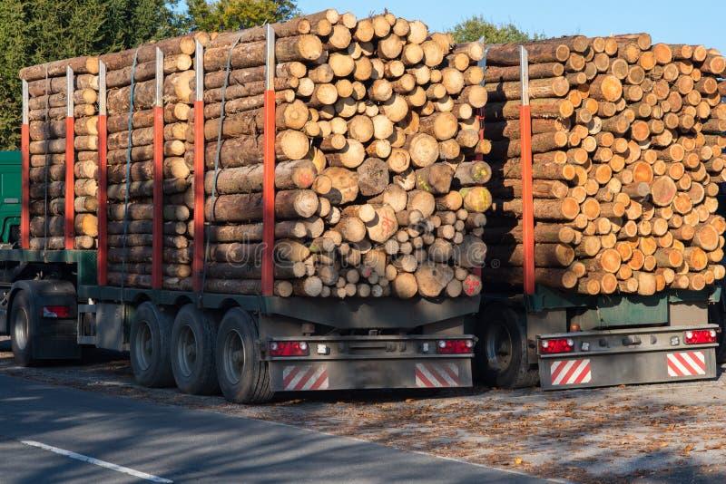 I camion hanno caricato con i tronchi di albero lungo il bordo della strada davanti alla a fotografia stock