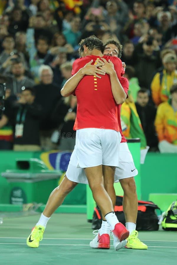I campioni olimpici Rafael Nadal e Mark Lopez della Spagna celebrano la vittoria al finale dei doppi degli uomini di Rio 2016 Oly immagine stock