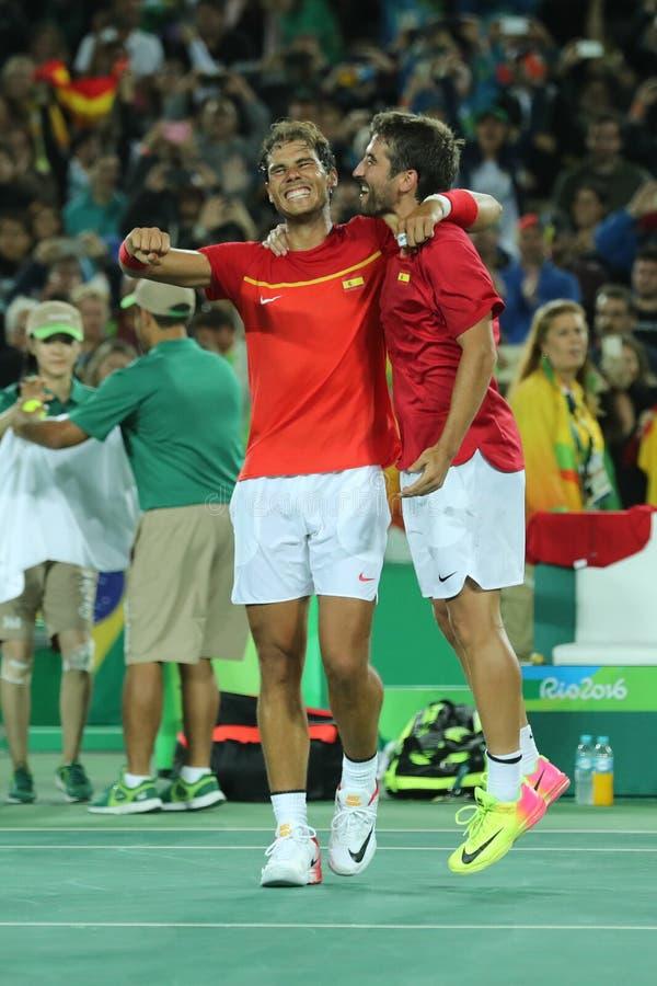 I campioni olimpici Rafael Nadal e Mark Lopez della Spagna celebrano la vittoria al finale dei doppi degli uomini di Rio 2016 Oly fotografia stock
