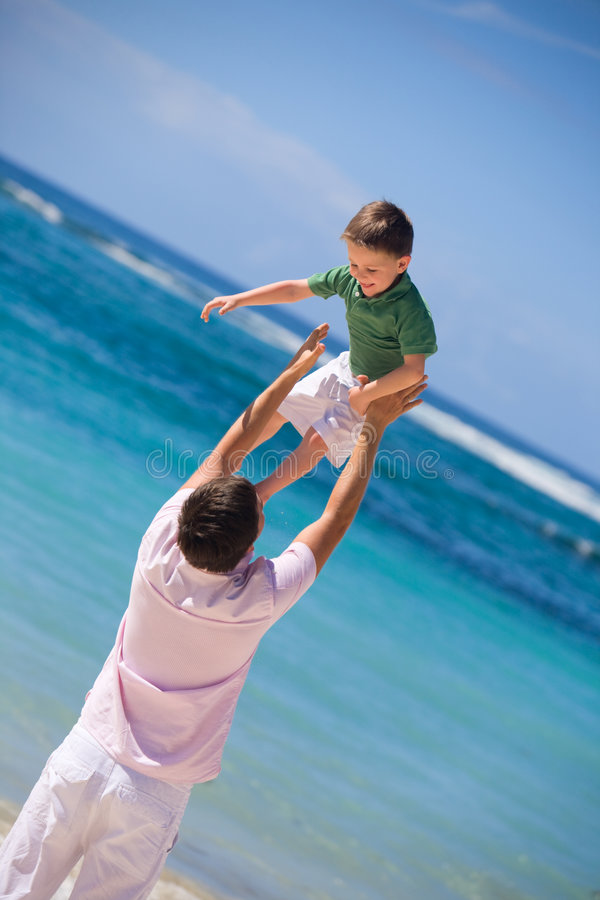 I Can Fly. Happy father and son on the beach stock photo