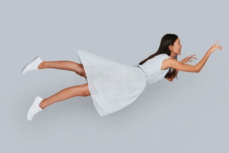 I can fly!. Beautiful young Asian woman smiling while hovering in air against grey background royalty free stock images