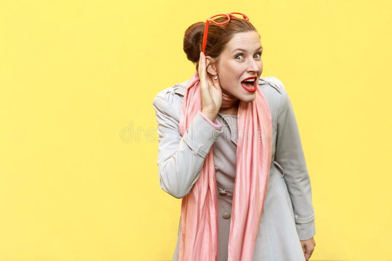 I can not hear you. Beautiful red head girl . Studio shot, yellow background royalty free stock image