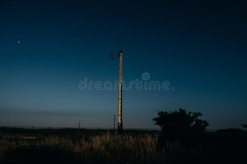 I can see you. PORTO, PORTUGAL - May 22, 2018: A bright telegraph pole standing tall against the blue hue of the night sky royalty free stock photos