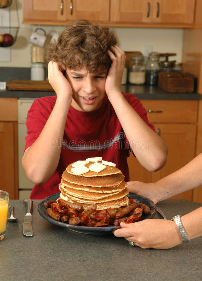 I can't eat all that!. Boy reacts in horror as Mom serves him an absurd amount of pancakes, bacon and sausage. Selective focus stock photo