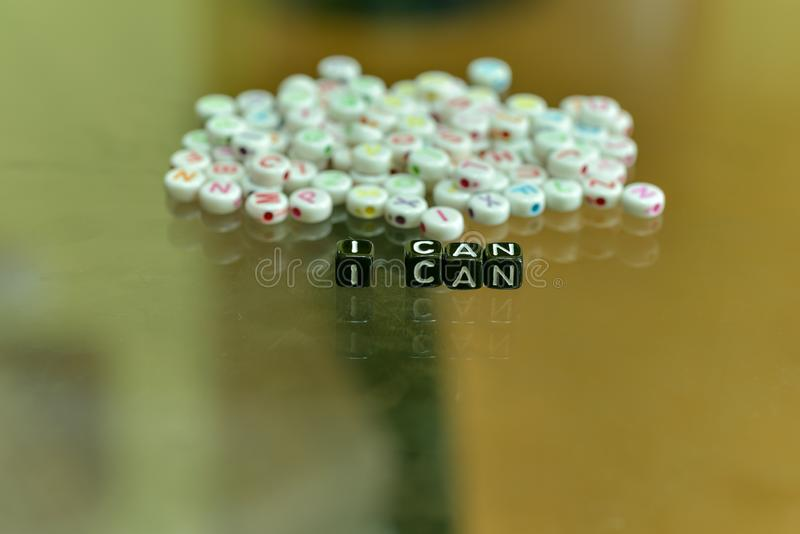 I CAN  written with Acrylic Black cube with white Alphabet Beads on the Glass Background.  royalty free stock image