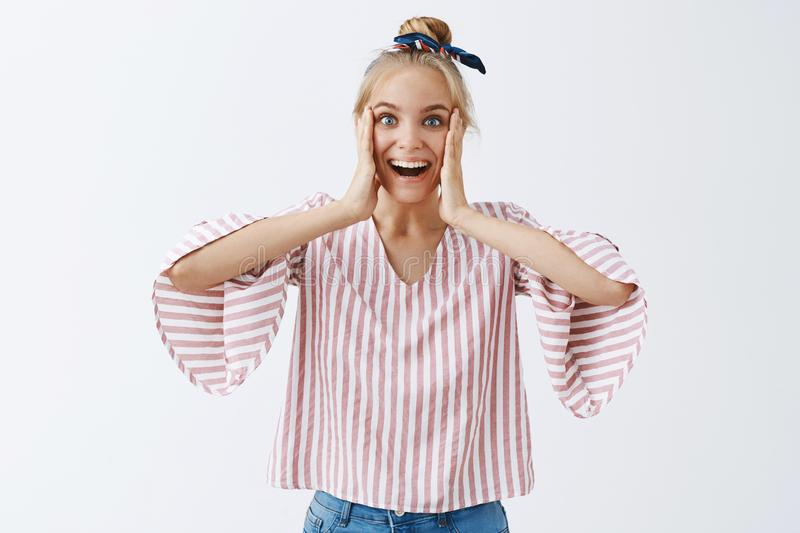 I cannot believe, amazed from surprise. Portrait of pleased and speechless happy female with blond hair in striped. Trendy blouse, holding palms on cheeks and stock photos