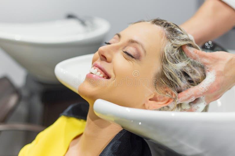 I capelli della donna bionda di lavaggio del parrucchiere immagini stock libere da diritti