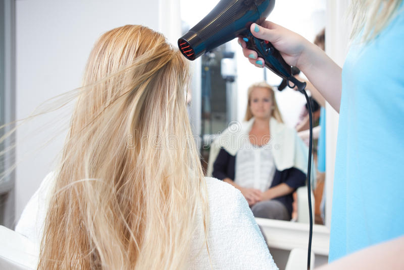 I capelli della donna di secchezza dello stilista nel salone di bellezza fotografia stock