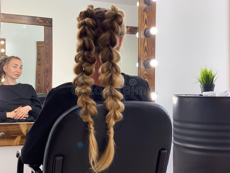 I capelli della donna intrecciante del parrucchiere nel salone di lavoro di parrucchiere fotografia stock libera da diritti