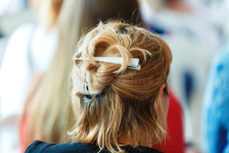 I capelli di scarsit? tinti della ragazza sono limitati con una molletta del ferro La vista della parte posteriore dei capelli de immagini stock libere da diritti
