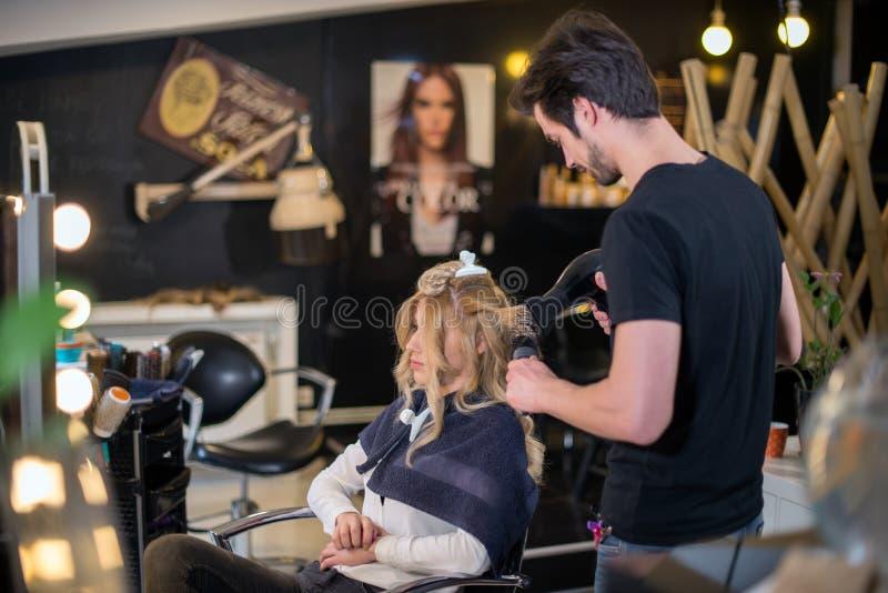I capelli di secchezza in salone, ragazza stanno preparandosi immagine stock libera da diritti