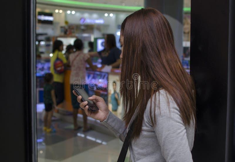 I capelli graziosi di signora riguardano l'invio di messaggi di testo del fronte di smartphone dentro il grande magazzino immagini stock