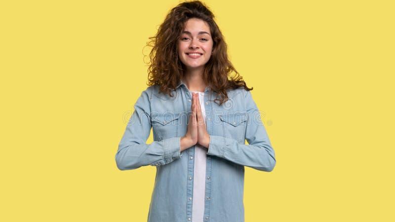 I capelli lanosi castana guardano in camera, sorridono, si tengono per mano nel gesto di preghiera immagini stock