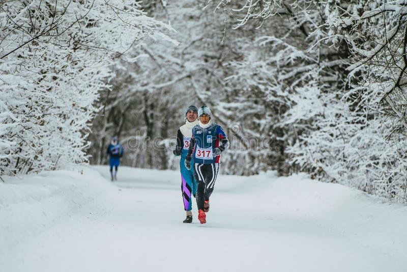 I capi degli atleti della corsa funzionano sulla pista nella foresta dell'inverno fotografia stock libera da diritti