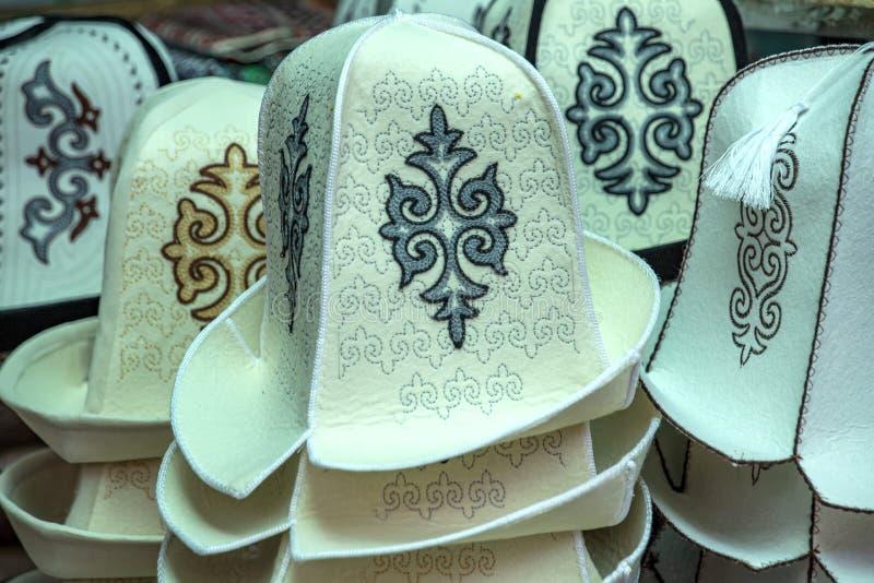 I cappelli chirghisi del copricapo hanno fatto di feltro con un ornamento nazionale mercato Corsa kyrgyzstan fotografia stock libera da diritti