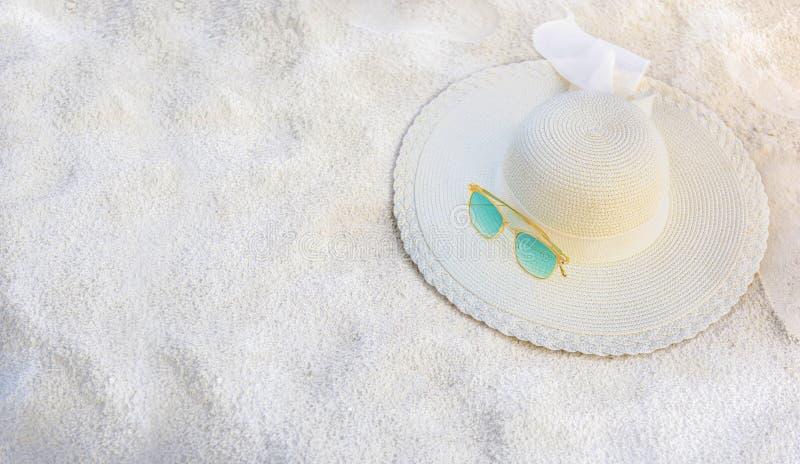I cappelli ed i vetri sono situati sulla spiaggia, mare blu, durante il giorno di rilassamento o delle feste lunghe fotografia stock libera da diritti