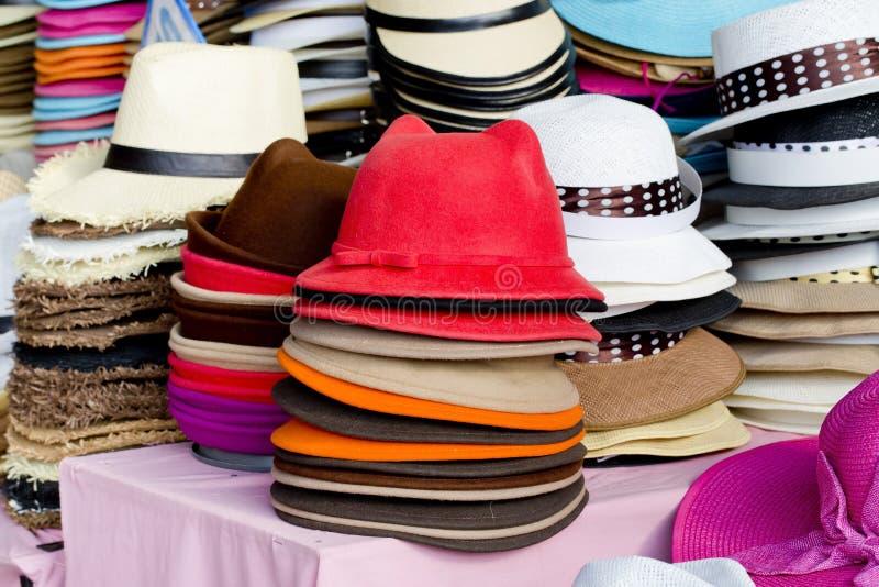 I cappelli femminili variopinti dell'estate si trovano sul contatore fotografie stock