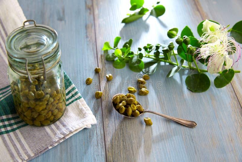 I capperi marinati con la pianta e la pianta del cappero fioriscono fotografie stock