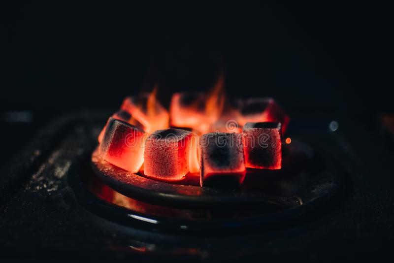 I carboni caldi per Shisha si sono scaldati sulla stufa in una barra del narghilé fotografia stock libera da diritti