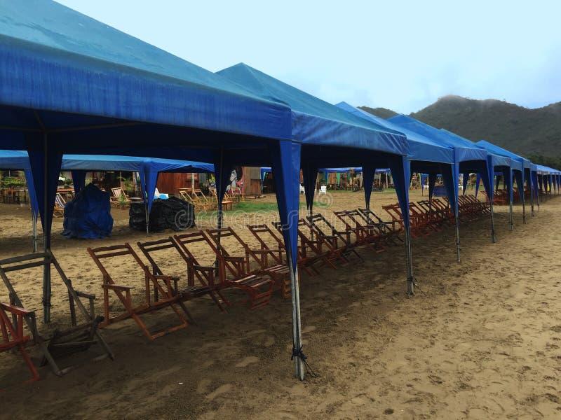 I carichi delle tende blu della spiaggia e delle sedie di spiaggia di legno hanno allineato sulla spiaggia fotografie stock libere da diritti