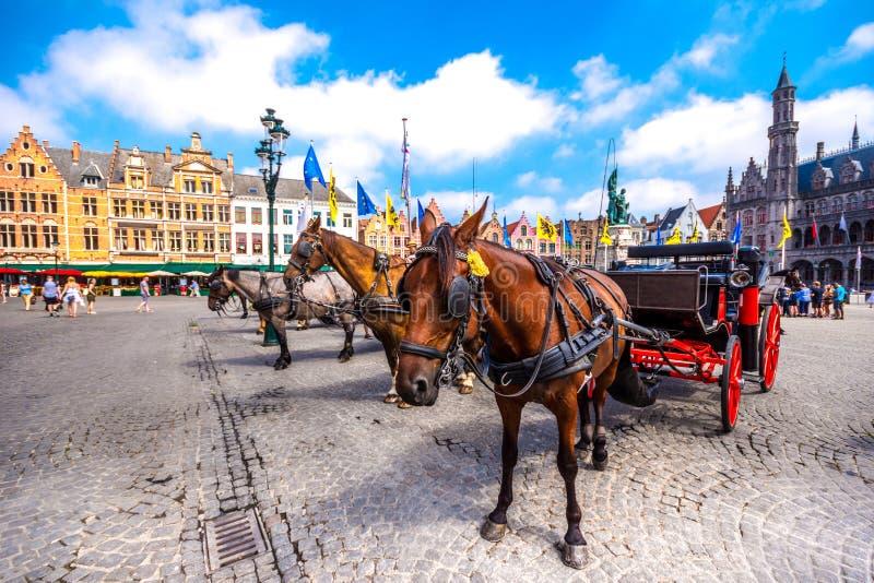 I carrelli del cavallo su Grote Markt quadrano in città medievale Bruges alla mattina, Belgio immagine stock