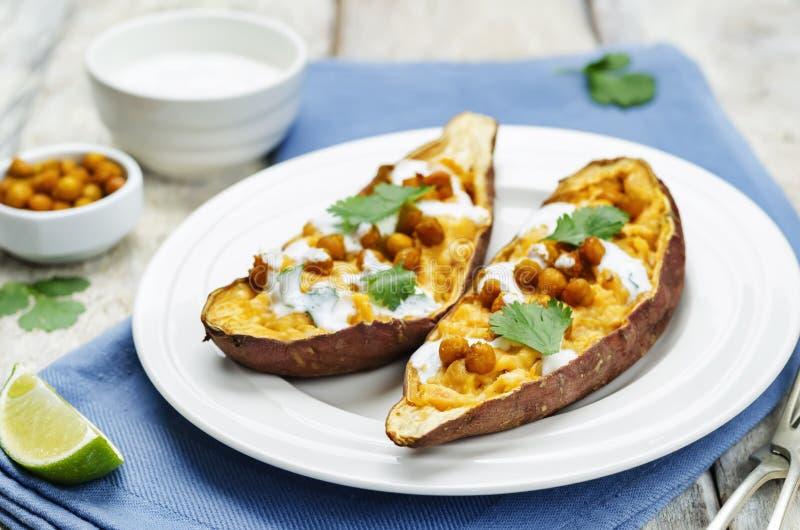 I ceci arrostiti hanno farcito la patata dolce con il cilantr greco del yogurt fotografia stock libera da diritti