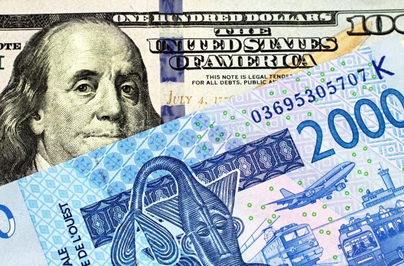 I cento dollari americano Bill With A Franc Banknote dell'Africa Occidentale fotografia stock libera da diritti