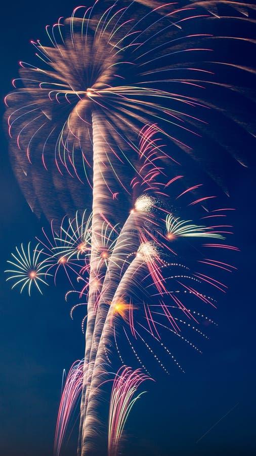 I cerchi multipli luminosi dei fuochi d'artificio di interrompono il cielo blu immagini stock