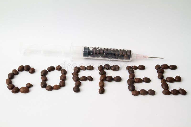 i chicchi di caffè arrostiti ed i chicchi di caffè hanno riempito la siringa sulla tavola fotografia stock libera da diritti
