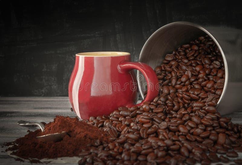 I chicchi di caffè si sono rovesciati da un barattolo di latta su una tavola di legno Vicino al caffè macinato del tazza di Borgo immagine stock libera da diritti