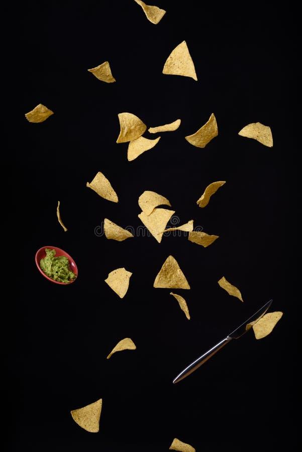 I chip di cereale della tortiglia dei nacho con guacamole fresco sauce il volo, fondo nero immagini stock