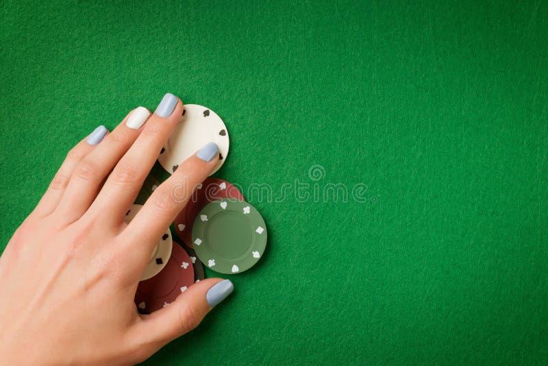 I chip di mazza della tenuta della mano della donna sul casinò verde hanno ritenuto il fondo immagini stock libere da diritti