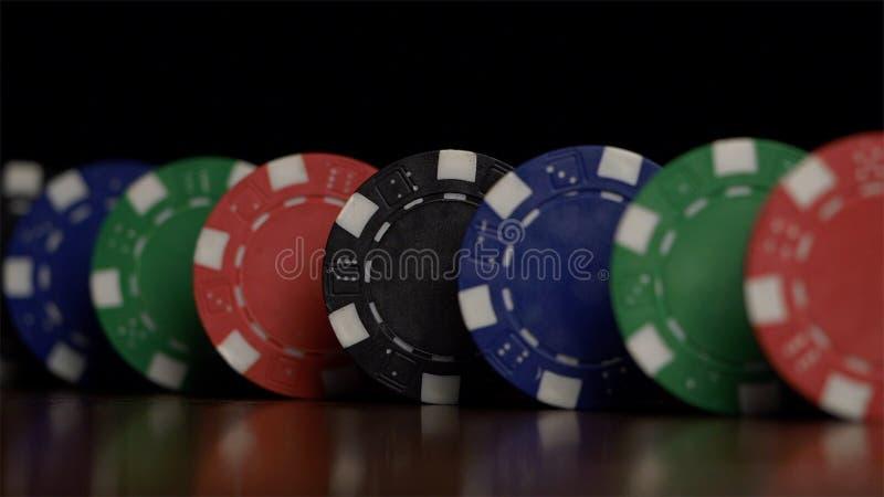 I chip di mazza stanno in una fila su un fondo nero, un effetto di domino Giocando il poker i chip sono sulla tavola, un simbolo  immagini stock libere da diritti