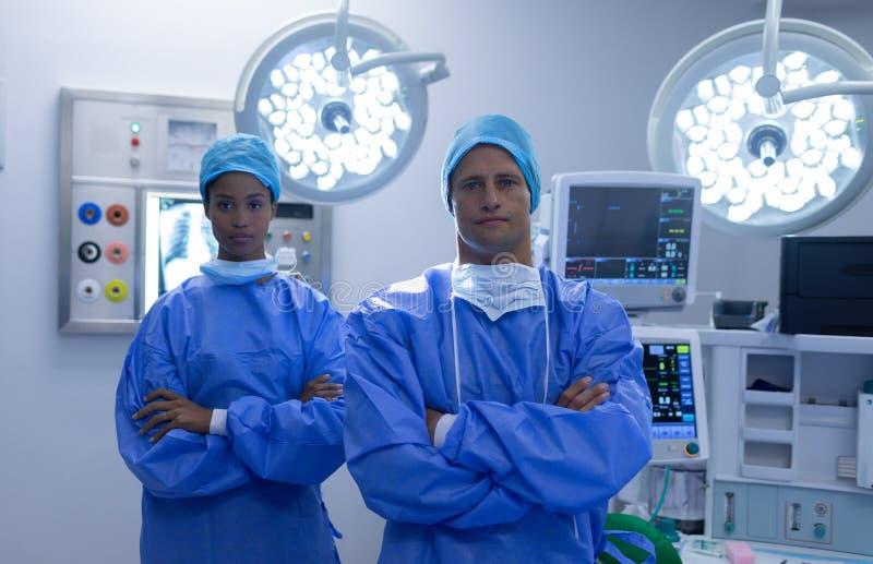 I chirurghi che stanno insieme alle armi hanno attraversato il teatro in funzione fotografia stock libera da diritti