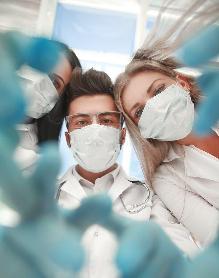 I chirurghi del gruppo stanno realizzando un'operazione facendo uso degli strumenti medici, in una sala operatoria moderna, immagine stock