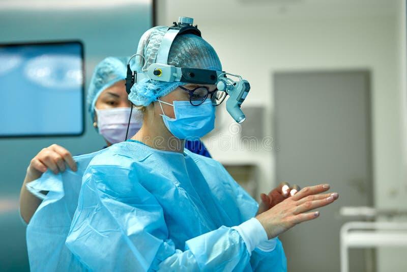 I chirurghi indossano l'abbigliamento sterile prima di chirurgia Un gruppo dei chirurghi che preparano per la chirurgia, ha insta fotografia stock