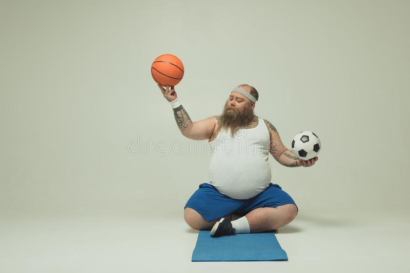 Concentrated fat man playing with two balls stock images