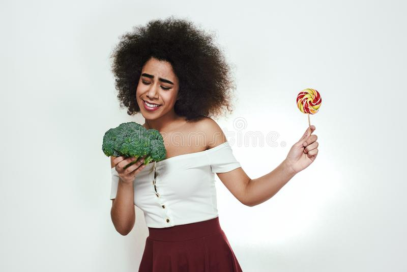 I choose healthy food! Pretty afro american woman is facing a choice of healthy broccoli or lollipop and looking at stock photos