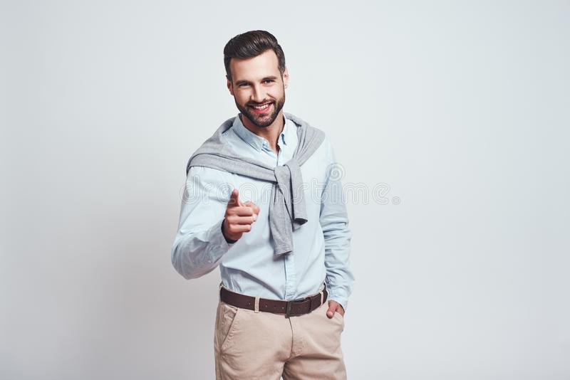 I choose you. Happy and smiling handsome man pointing his finger and looking positive at camera while standing against stock image