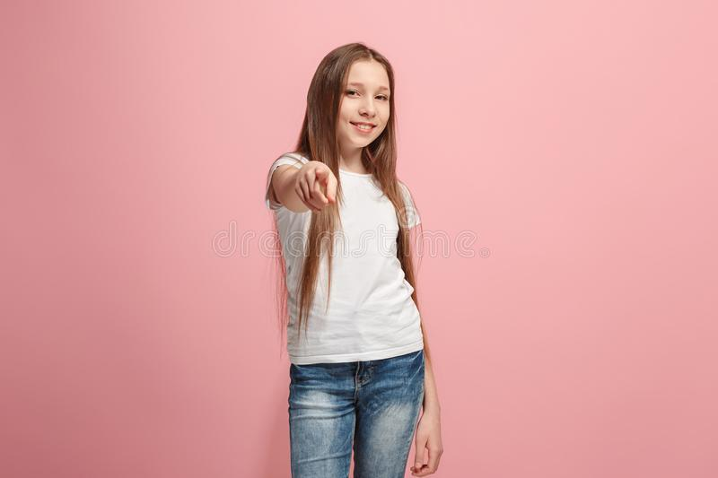 The happy teen girl pointing to you, half length closeup portrait on pink background. stock photo