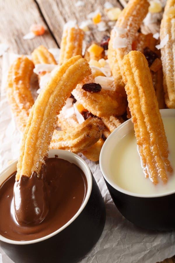 I churros dolci fritti nel grasso bollente sono servito con il primo piano del latte condensato e della cioccolata calda vertical fotografia stock
