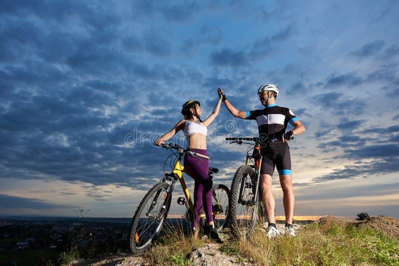 I ciclisti di paia sopra la montagna si danno il livello cinque contro il cielo nuvoloso al tramonto immagini stock libere da diritti