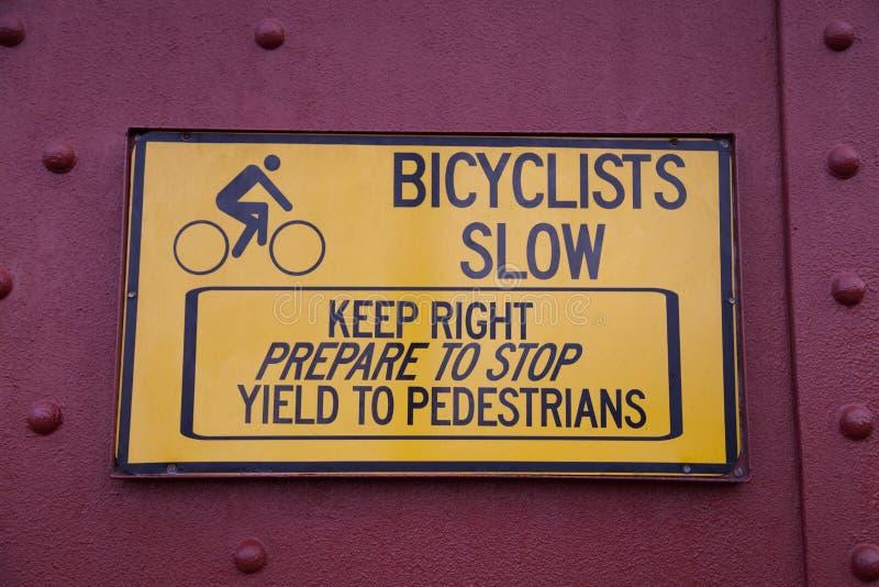 I ciclisti rallentano il segno immagini stock