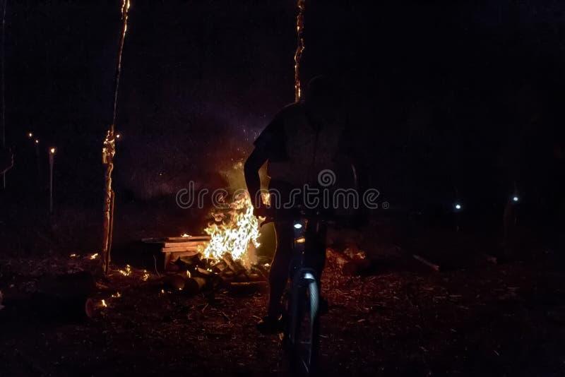 I ciclisti saltano su una bicicletta sopra un fuoco alla notte fotografie stock libere da diritti