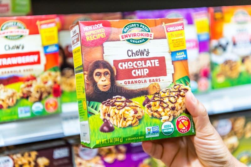 I clienti passano la tenuta del pacchetto della marca di Environkidz del percorso della natura di barre di granola libere di pepi fotografia stock