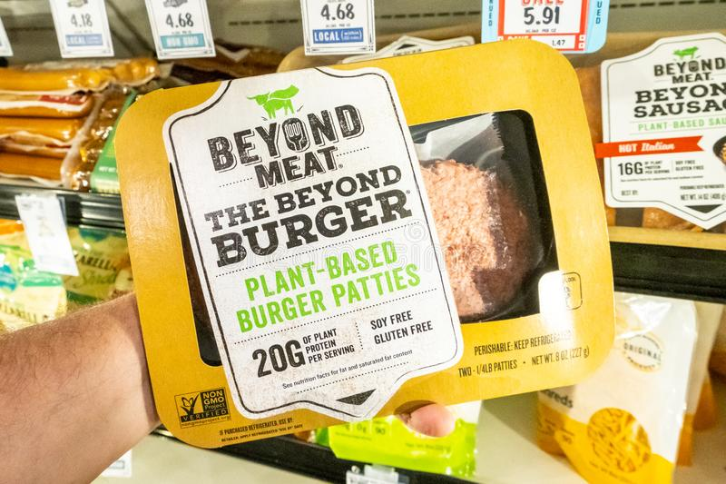 I clienti passano la tenuta del pacchetto della pianta di marca della carne di Beyong hanno basato i tortini dell'hamburger immagine stock