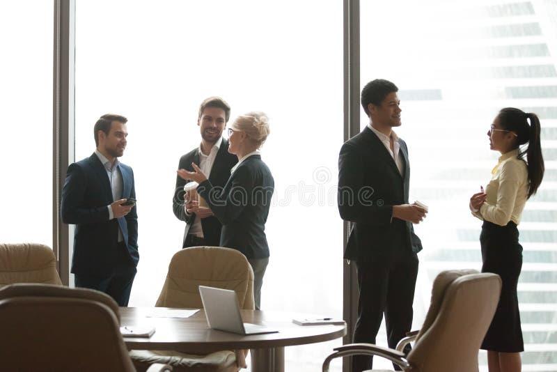 I colleghi che hanno conversazione casuale durante il lavoro irrompono l'ufficio fotografia stock