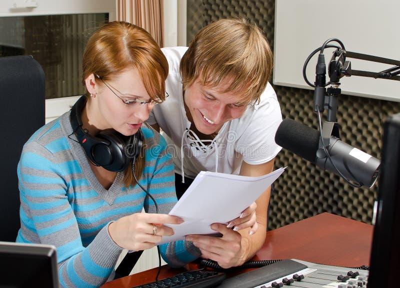 I colleghi esaminano la lista di radiodiffusione fotografia stock